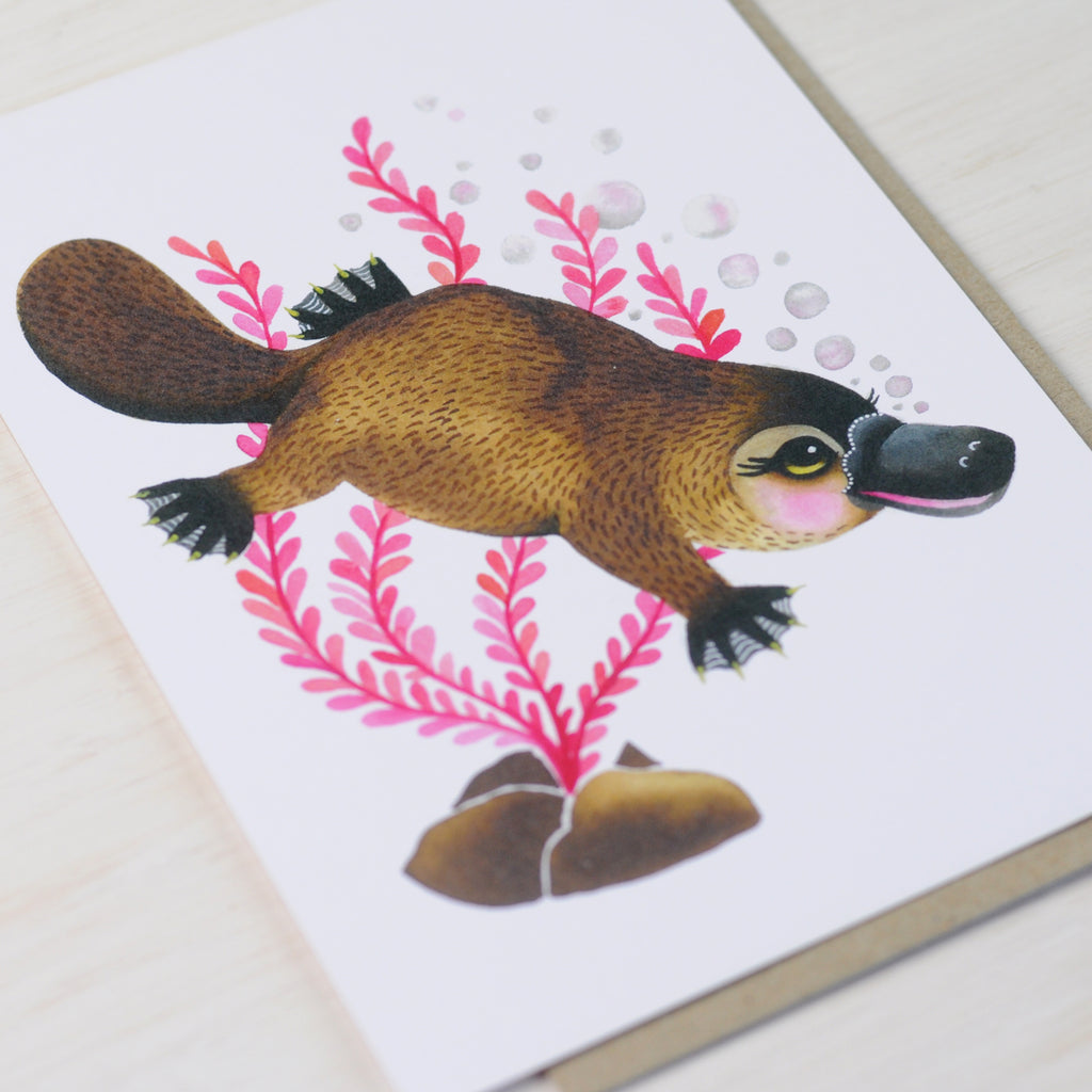 Greeting card featuring a cute swimming platypus