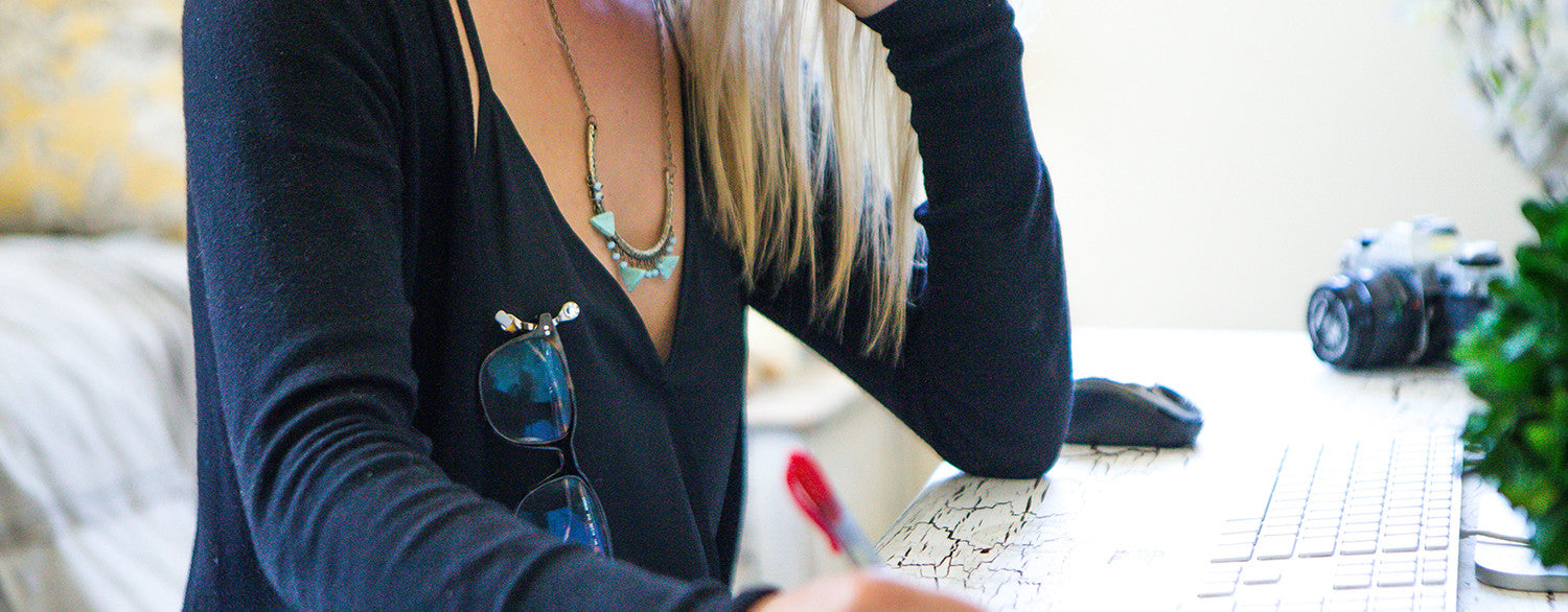 Blonde haired women wearing an swarovski crystal magnetic eyeglass holder, black camisole and sweater, while working at a white wood desk