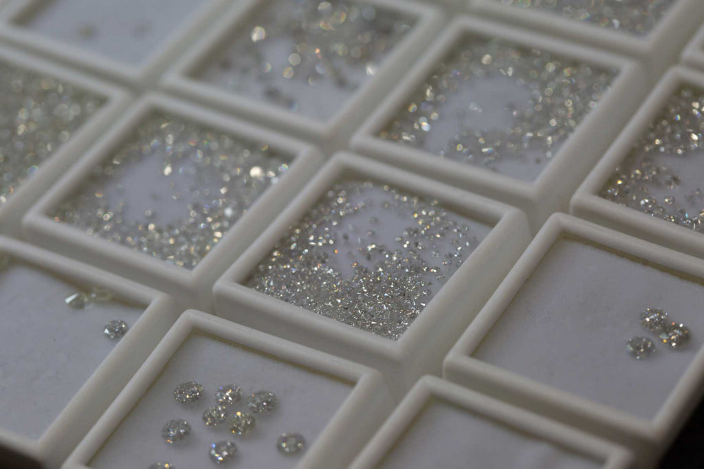 Various white diamond melee in display boxes for pavé setting