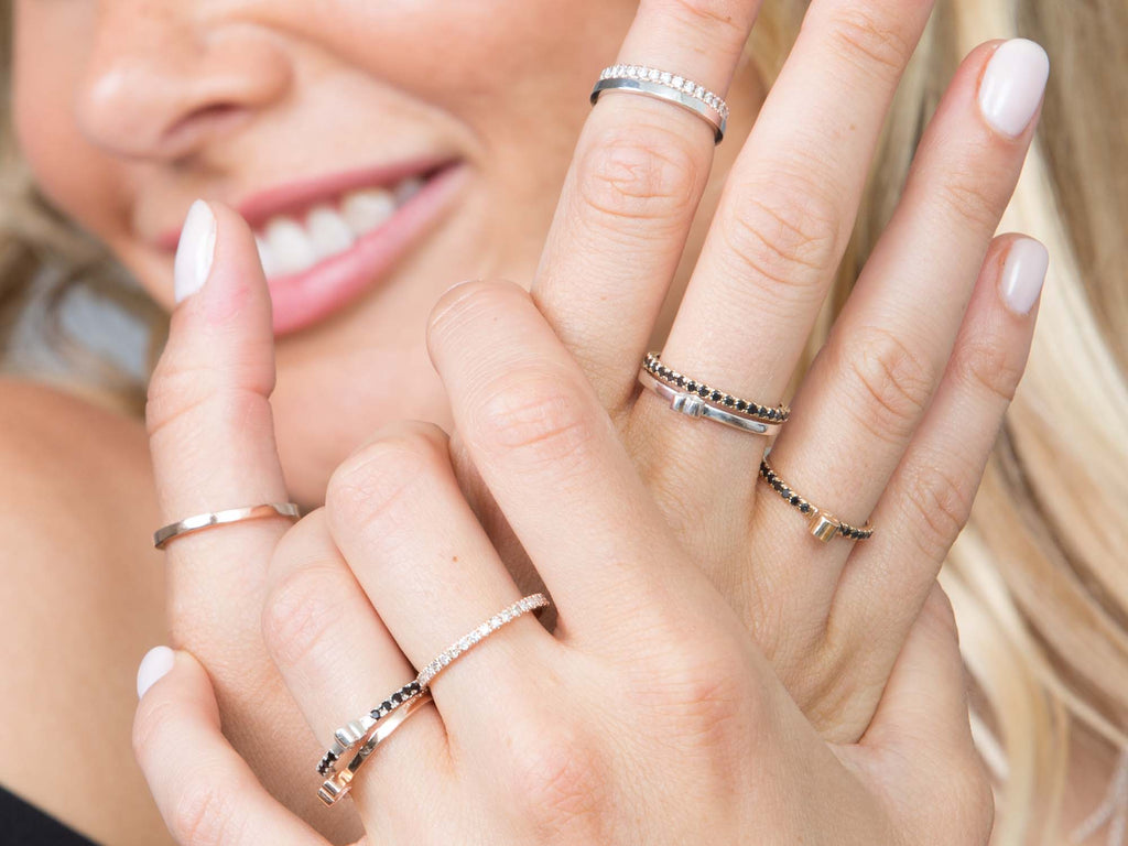 A girl wears stacks of mixed metal rings