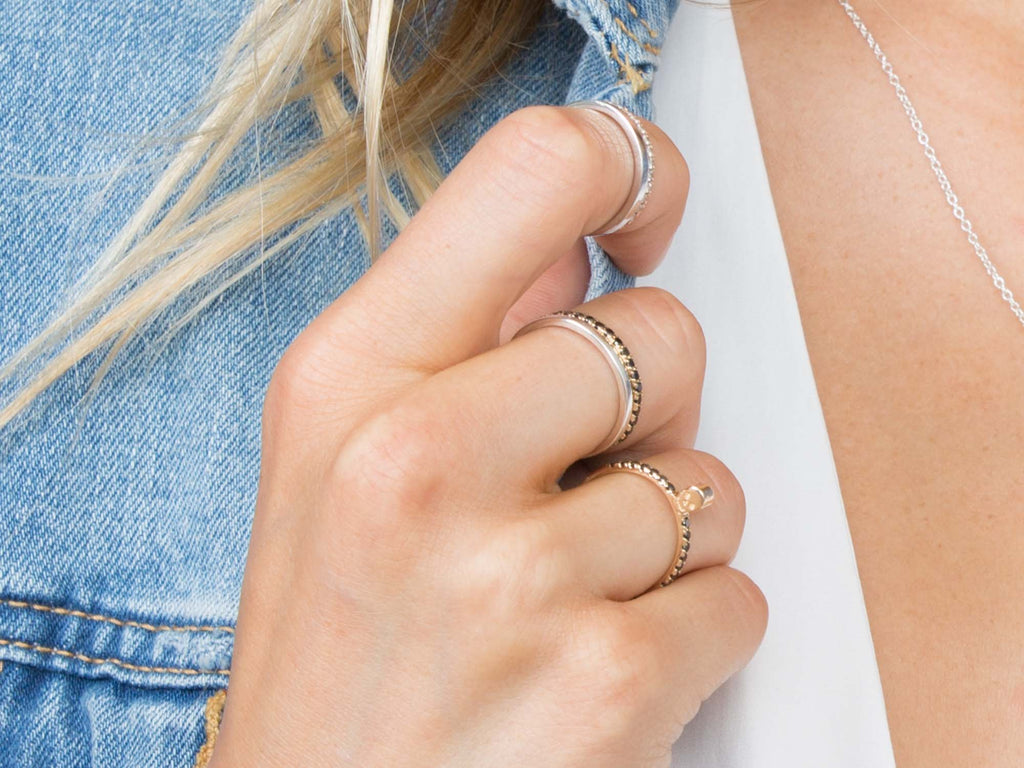 a girl wears a mix of stacking rings