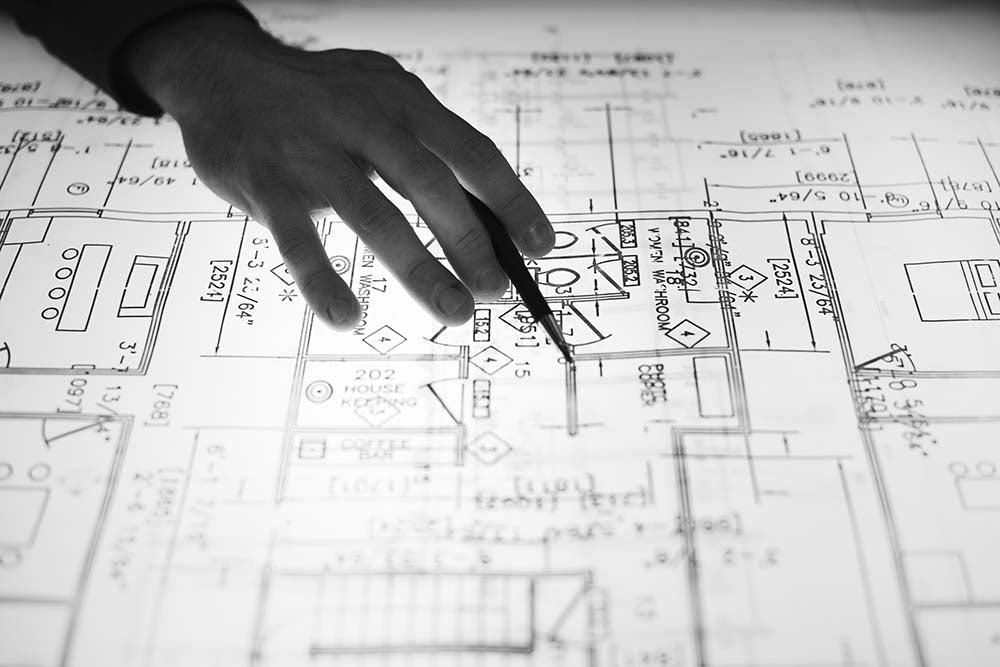 a person's hand over a blueprint