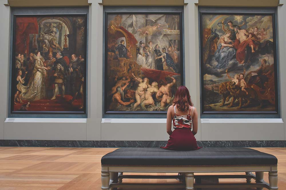 a girl sits in a museum looking at paintings