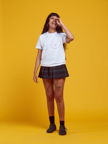 laughing girl wearing white loose t-shirt with embroidered boobs and tartan mini skirt. she has tattoos and long black hair