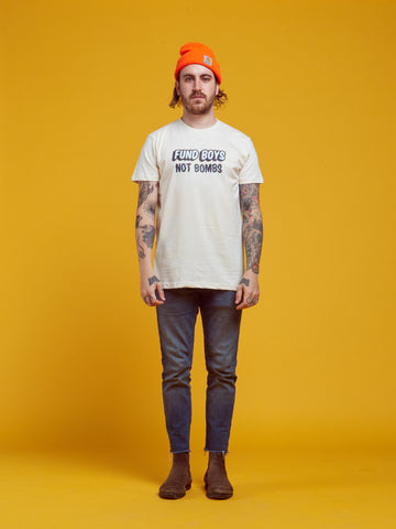 "a man is standing against a yellow backdrop. he has an orange beanie hat, blue jeans, and a t-shirt that is printed with the words ""fund boys not bombs"""