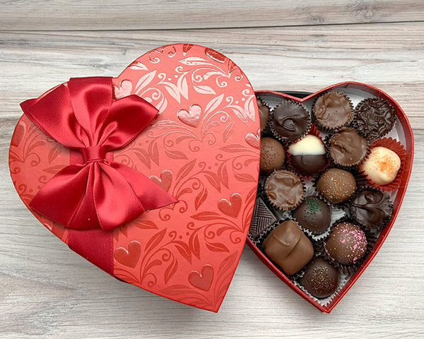 Shiny red heart box filled with chocolates
