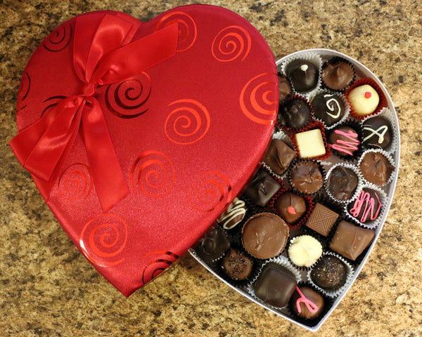 Red satin heart box filled with chocolates