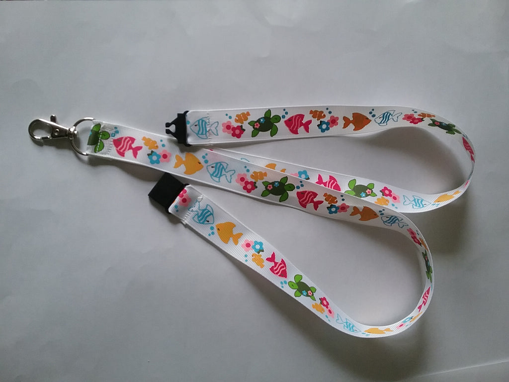 Lanyard made with white ribbon with lots of fish as the pattern it has a safety breakaway lanyard id or whistle holder - Tilly Bees