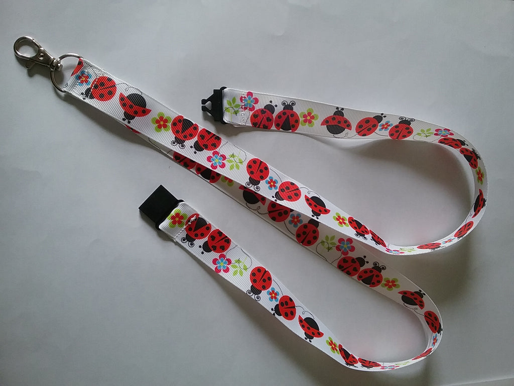 Lanyard made with white ribbon with lots of red ladybirds as the pattern it has a safety breakaway lanyard id or whistle holder - Tilly Bees