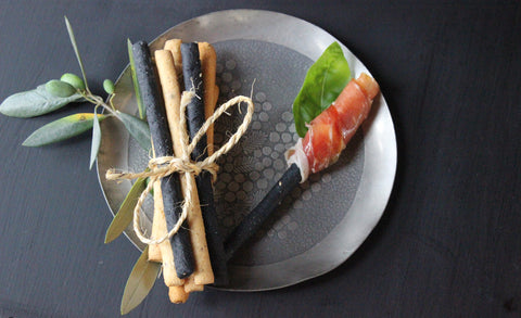 grissini on plate with charcuterie