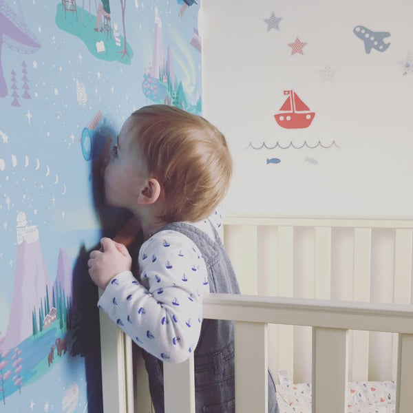 Little boy kissing his Renn Designs Northern Lights wallpaper