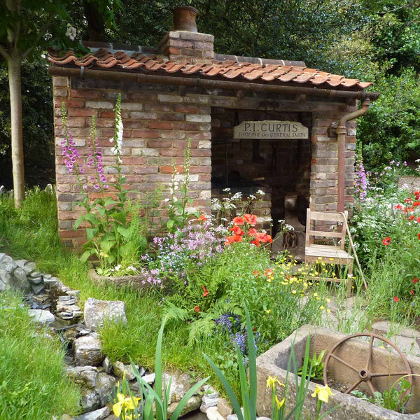 Show Garden with small brick building at Chelsea Flower Show