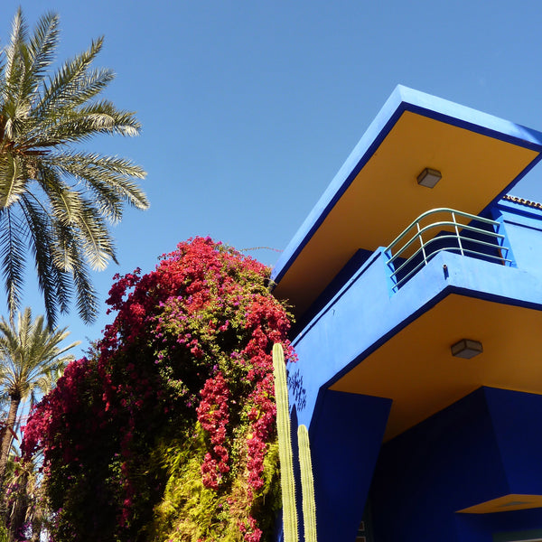 Marjorelle Gardens with blue building, palm trees and borgainvillea