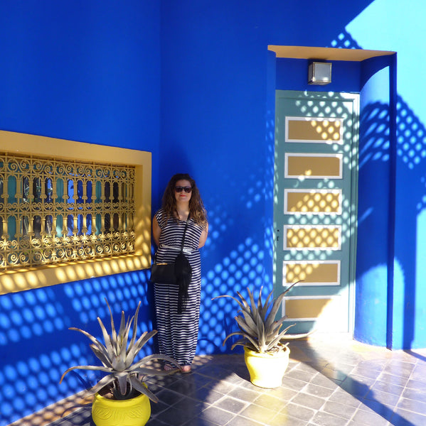 Blue and yellow architecture in Marjorelle Gardens, with woman in patterned shadows