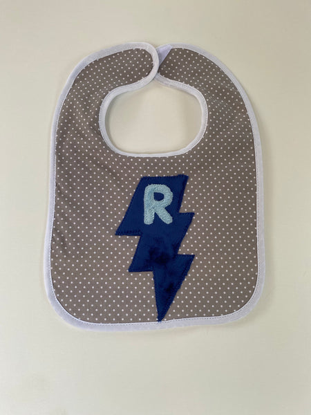 Tiny dot bib with light blue initial and navy blue lightning bolt