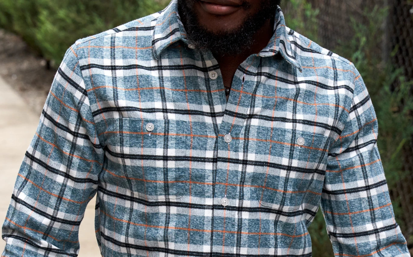 A close-up shot of a young man wearing an Ash & Erie multi-colored button-down shirt with brushed fabric.