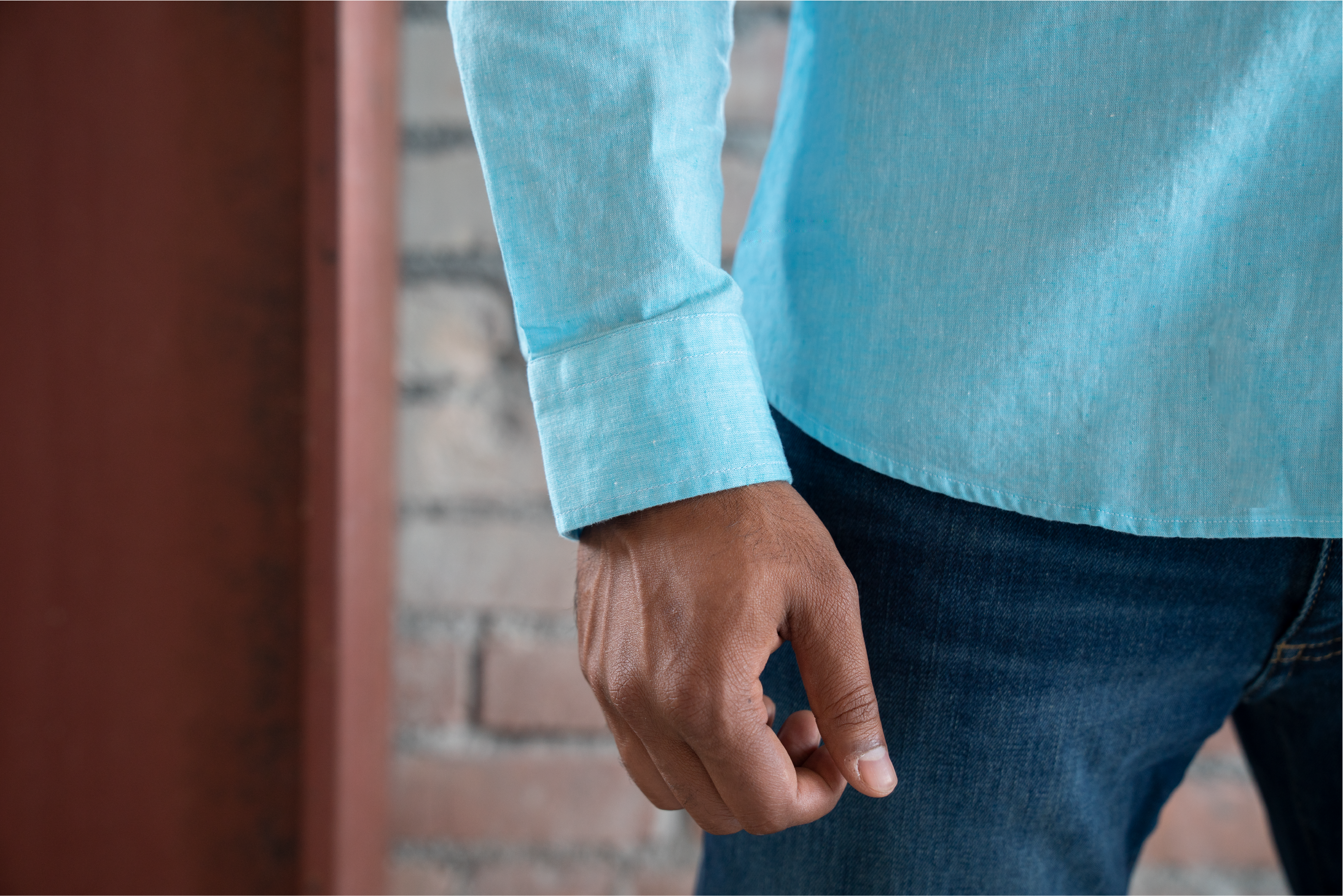 A close-up image of a young man's wrist to accentuate the Ash & Erie button-down shirt's correct sleeve length.
