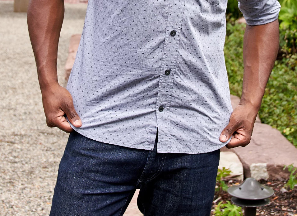 An image of a young man posing for a camera while pulling down on his Ash & Erie button-down everyday shirt.