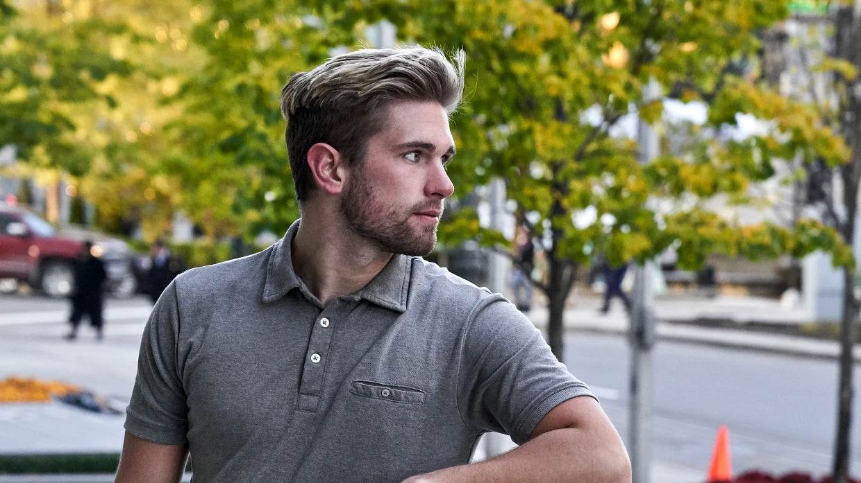 A young man looking off to the side while wearing a grey Ash & Erie polo.