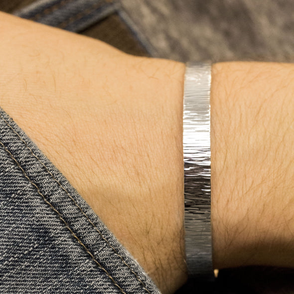 Man wearing a personalized men's cuff bracelet in sterling silver