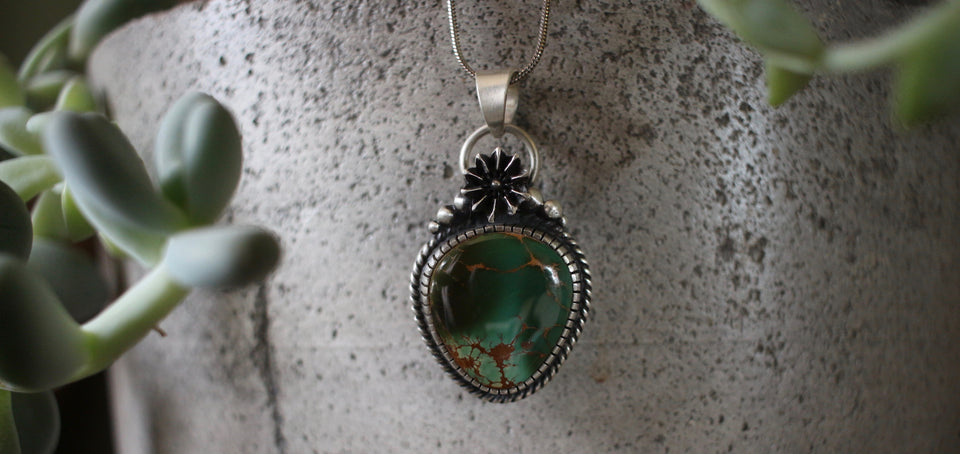 dark green royston pendant set in sterling silver with seed pod