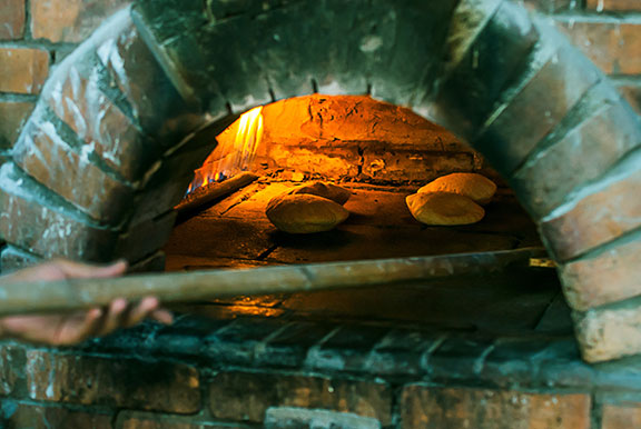 Cooking  bread in a brick pizza oven