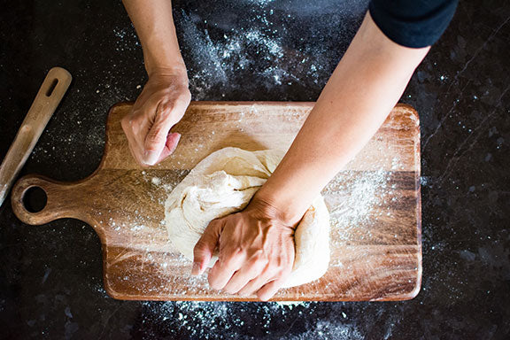kneading pizza dough in preparation for the wood-fired pizza oven