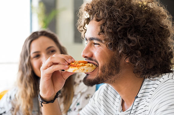 man enjoying slice of pizza