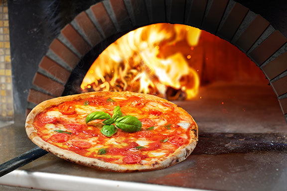 pizza coming out of a commercial wood-fired pizza oven