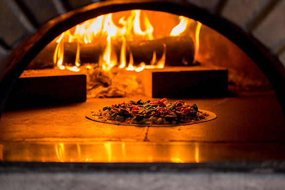 pizza inside wood-fired oven