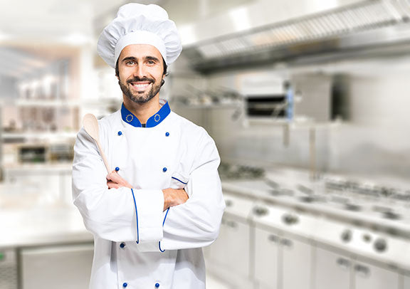 smiling chef standing in restaurant kitchen