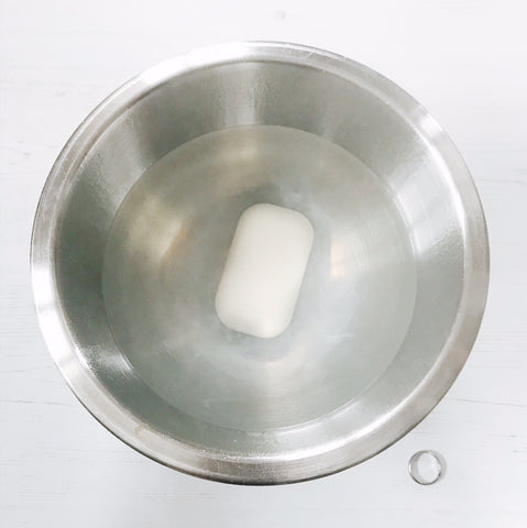 A bar of soap in a bowl of boiling hot water a silver ring by its side