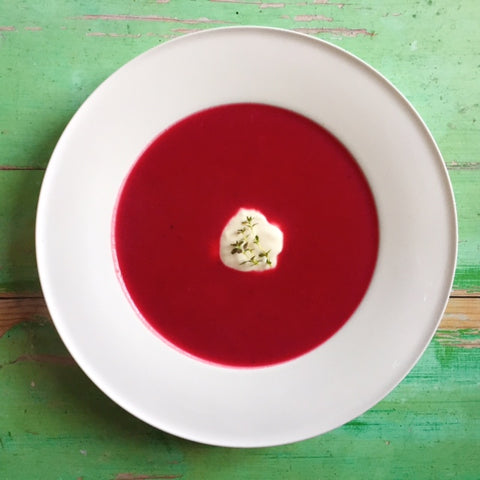 Beetroot soup with sour cream and herbs on green table