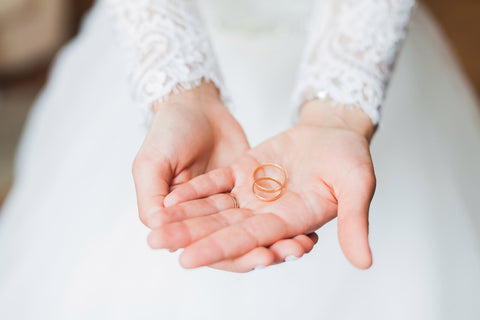 Wedding rings held by bride's hands