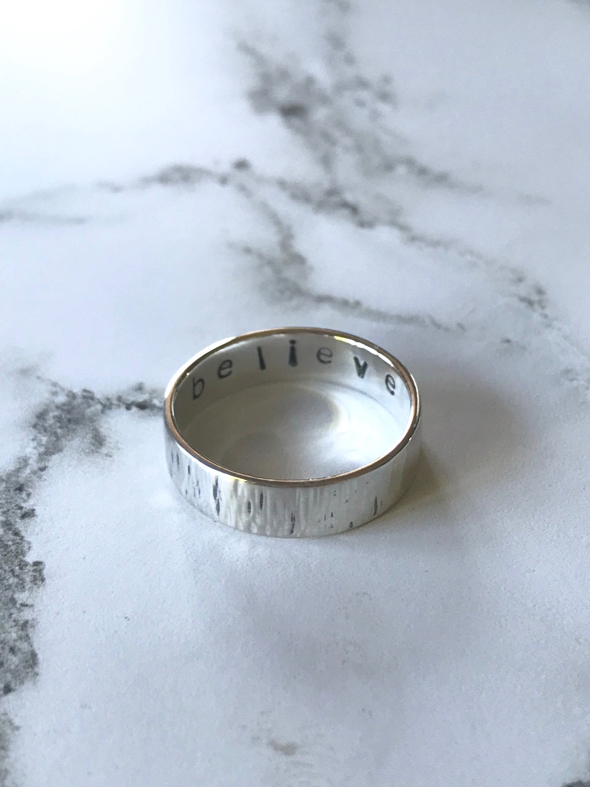 Empowering silver ring with striped texture