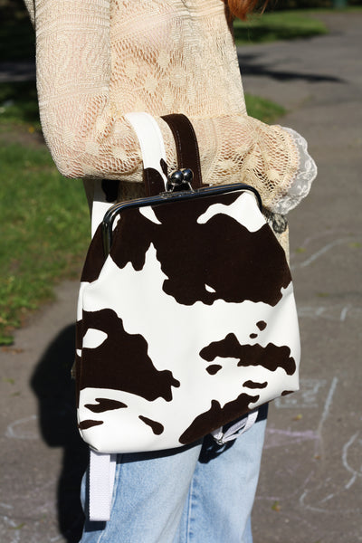 close up of girl with cow print backpack