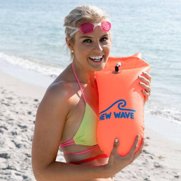 woman manequin wmiling on the beach and holding a open water swim buoy of New Wave Brand