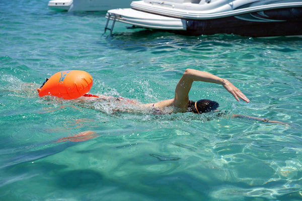 woman manequin in a pool holding a open water swim buoy of New Wave Brand