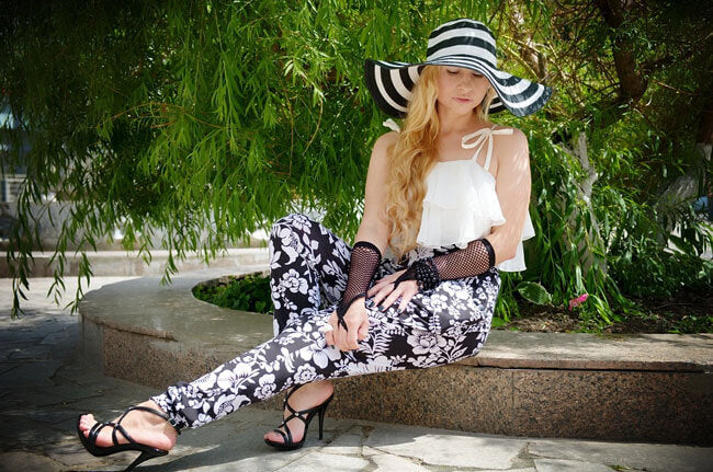 Woman in flower print pants, striped hat, and lace gloves