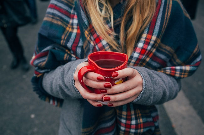 Woman in a sweater and scarf holding a mug of tea