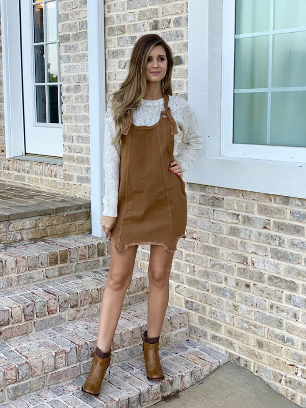 Woman in brown overall dress and brown boots