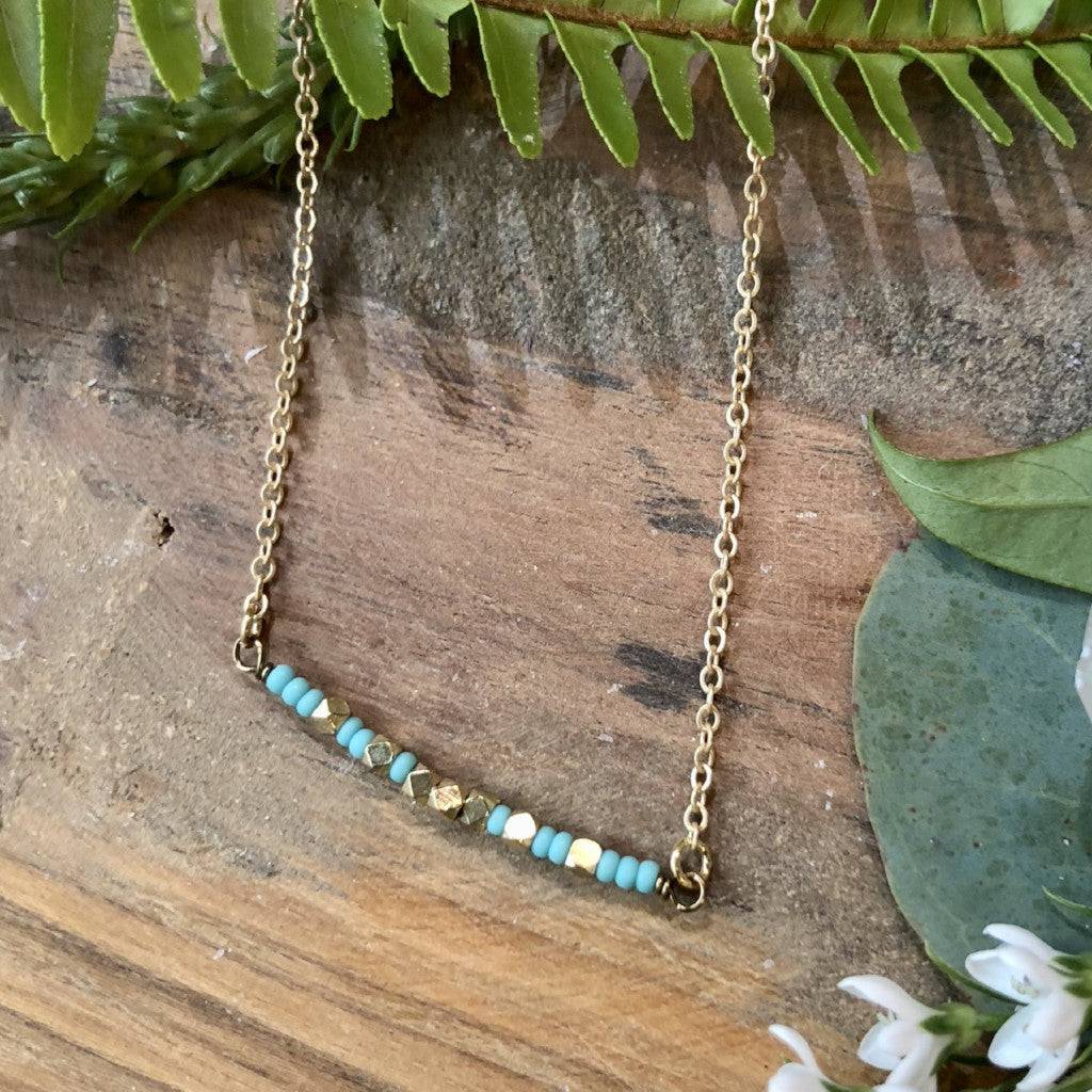 "Matte turquoise and brass beaded small stream necklace on a 16-18"" adjustable matte gold chain"