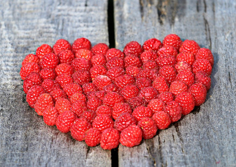 A heart made of freshly picked raspberries on a wooden table