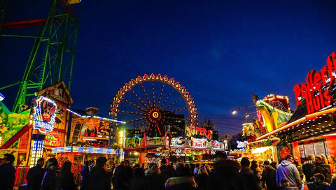 a county fair at night with light up rides like the ferris wheel & a carnival