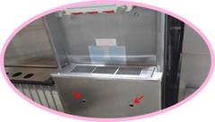 taylor soft serve frozen yogurt machine front panel under drip tray has red arrows pointing at holes where you can press the breaker reset button