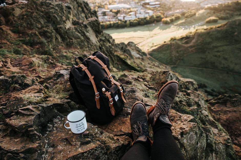 Black and brown backpack next to a white coffee cup on a huge rock