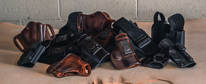 Pile of black and brown leather gun holsters