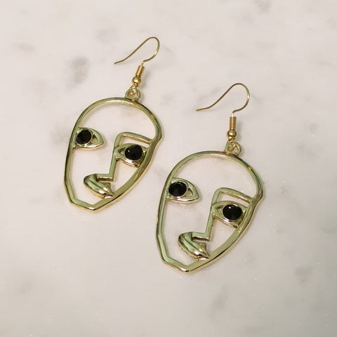 Gold face outline earrings with black eyes