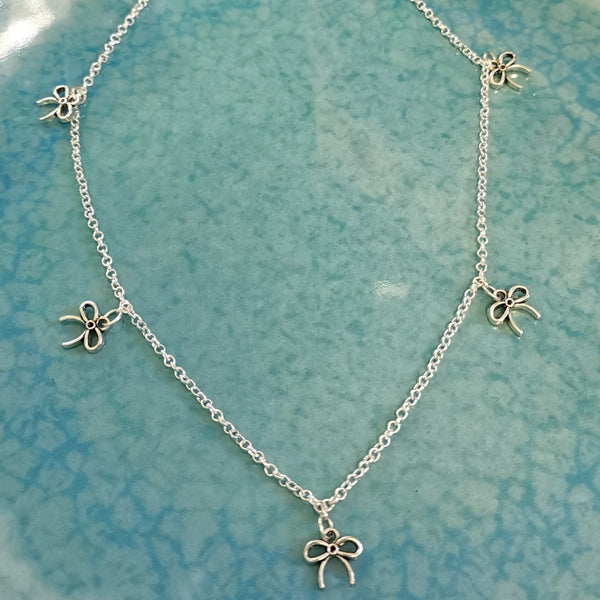 Pewter/Antique silver tone little bow multiple charm necklace