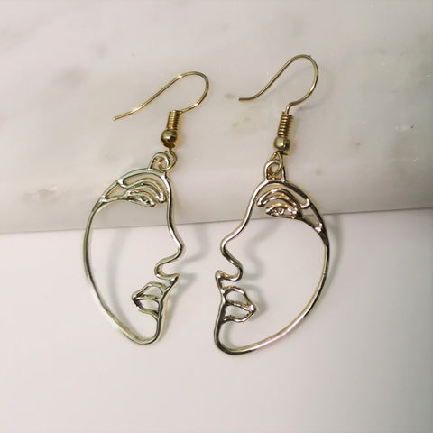 Gold face side profile earrings
